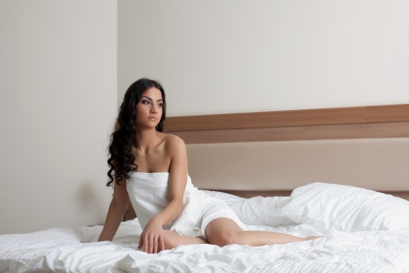 bed sheet: Portrait of beautiful brunette woman in white towel on bed