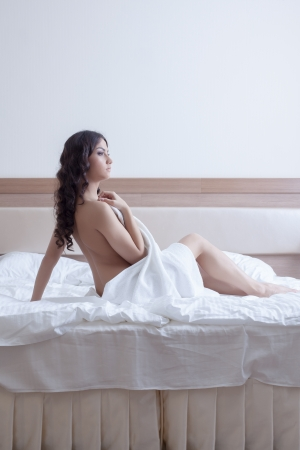 Portrait of beautiful brunette woman in towel on bed Stock Photo - 16565374