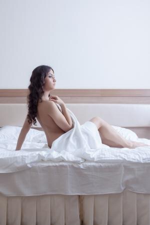 Portrait of beautiful brunette woman in towel on bed Stock Photo - 16565374