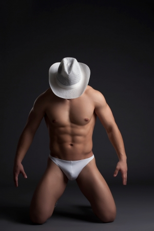 Sexy cowboy in white hat  Studio portrait