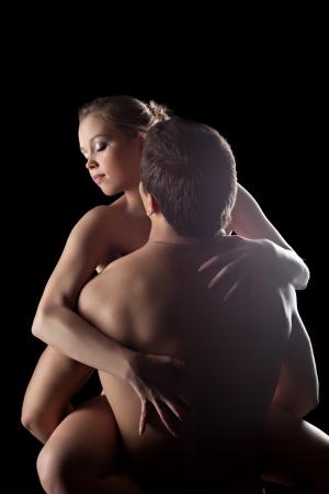 naked black women: Studio portrait of young couple having sex in dark