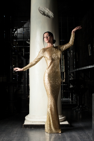 Full length portrait of fashion young woman in gold dress photo