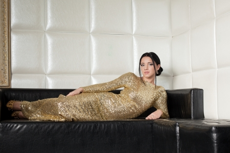 Glamour portrait of fashion brunette woman in gold dress photo