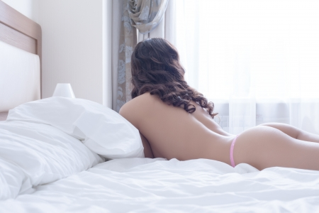 sexy woman on bed: Sexy brunette young woman lying on bed