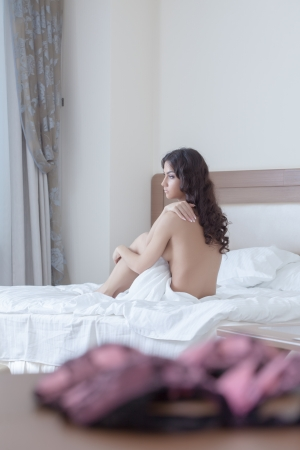 one sheet: Sexy brunette young woman sitting on bed