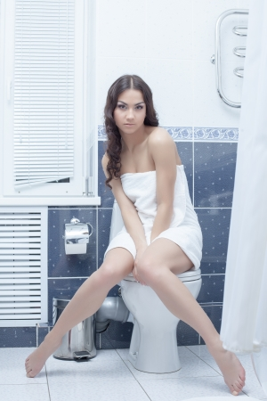 Portrait of brunette woman sitting on toilet bowl