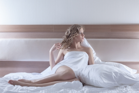 bed sheet: Full length portrait of sexy blonde woman sitting on bed