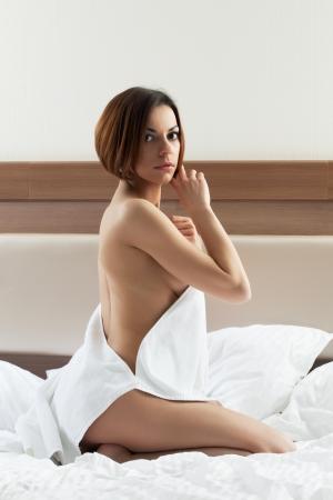 toalla: linda mujer joven morena llevar toalla y relajarse en la cama Foto de archivo