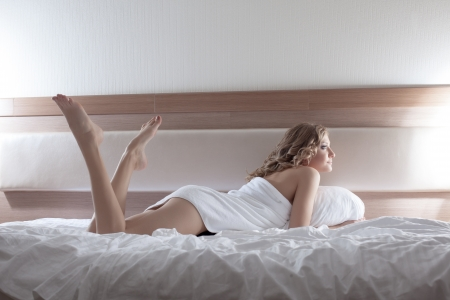 Full length portrait of sexy blonde woman lying on bed photo