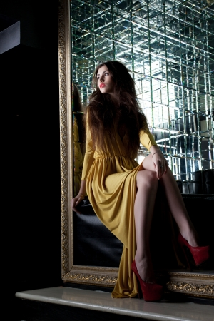 Full length portrait of brunette young woman in long dress in club Stock Photo - 17255303
