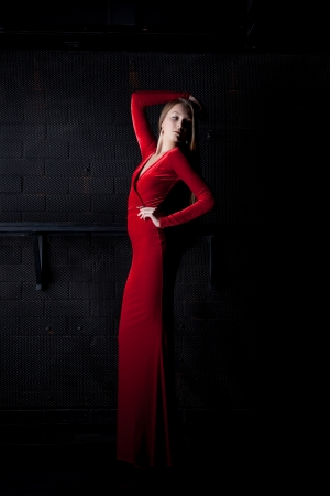 velvet dress: Full length portrait of beautiful woman in red long dress in dark club Stock Photo