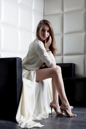 donna ricca: Ritratto di lunghezza completa di bella donna in abito bianco, seduta sul divano