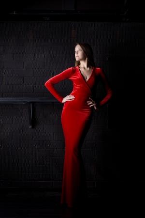 vestido de noche: Retrato de cuerpo entero de una mujer hermosa en vestido largo de color rojo en la oscuridad Foto de archivo