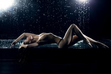 erotico: Ritratto di tutta la lunghezza di bella giovane donna distesa sotto la pioggia