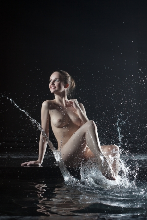 nude wet: Full length portrait of beautiful nude young woman near water in dark Stock Photo