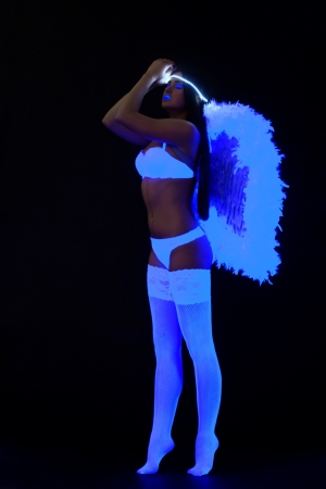 woman in sexy lingerie with fluorescent wing under ultraviolet light  photo