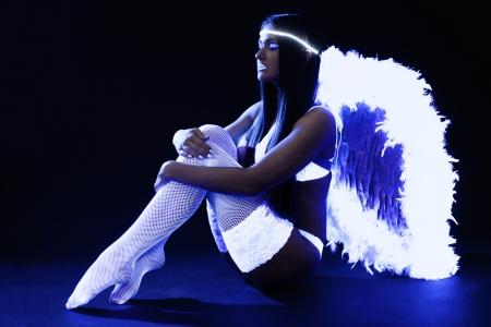 Full length portrait of pretty go-go girl in angel costume