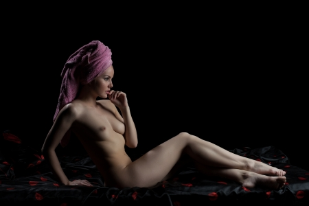 topless brunette: Full length portrait of nude young woman sitting on bed in dark bedroom