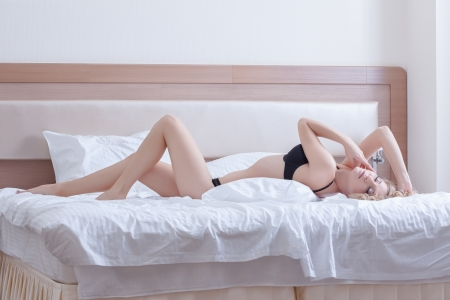 Full length portrait of sexy young woman in black lingerie lying on bed photo