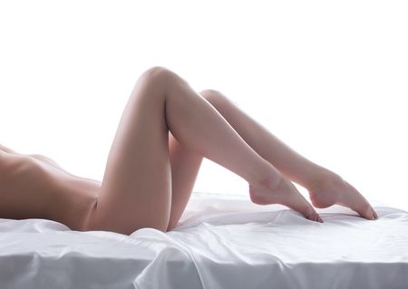 nude in bed: beautiful young woman legs on silk bed  Isolated on white Stock Photo