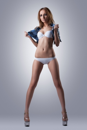 Sexy young woman in white bikini and denim jacket photo