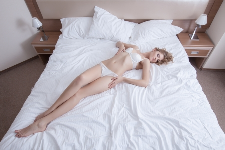 women in underwear: Full length portrait of beautiful blonde woman relaxing in bedroom Stock Photo