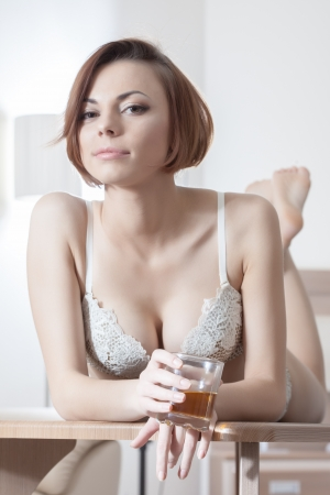Portrait of beautiful woman in beige lingerie relax with drink on hotel bedroom photo