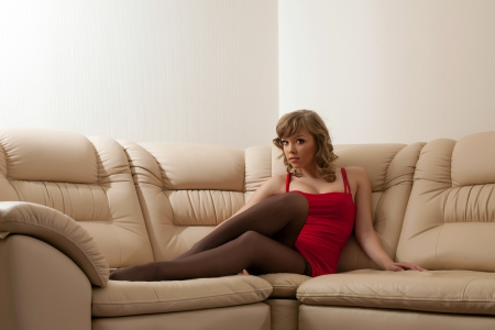 sexy stockings: Portrait of sexy young woman in red dress sitting on sofa