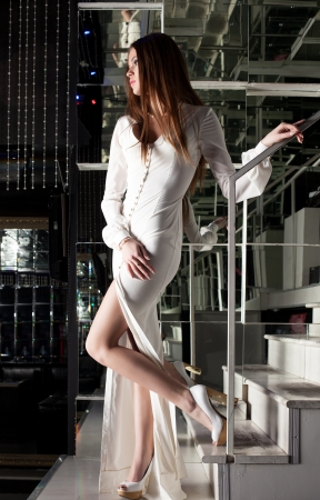 Full length portrait of pretty brunette woman in long white dress posing on stairs photo