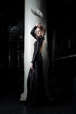Full length portrait of beautiful young woman in black dress near column