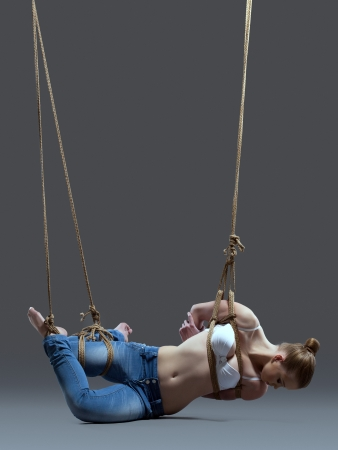 bondage woman: Full length portrait of young woman with shibari in studio