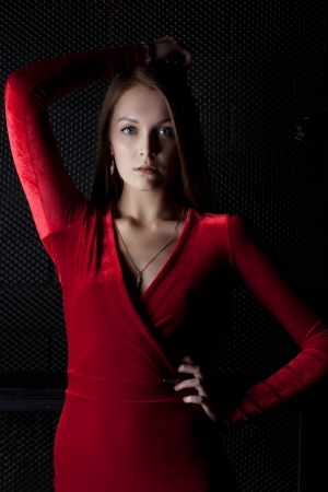 Portrait of beautiful young woman in red dress in dark room photo