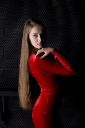 Portrait of beautiful young woman in red dress with long hairs photo