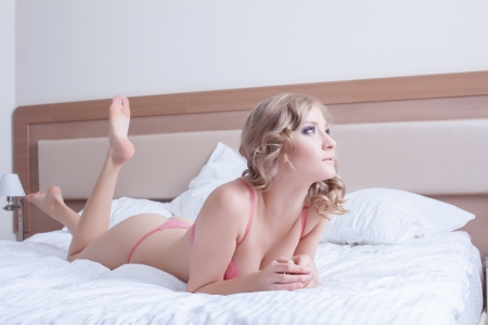 Full length portrait of sexy young woman in rose lingerie play with pillows on bed photo