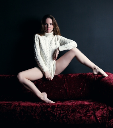 Studio portrait of young woman in white sweater sitting on sofa Stock Photo - 17533801