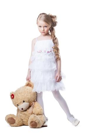 petite fille triste: Portrait en pied d'une petite fille triste avec le jouet mou Isolé sur fond blanc