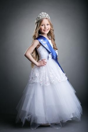 Full length portrait of pretty little girl in tiara and long white dress photo