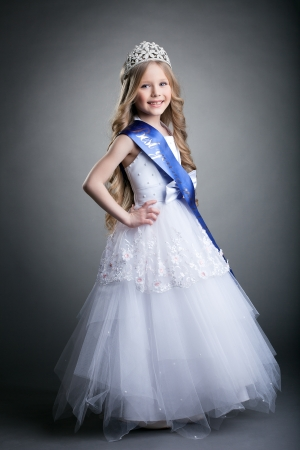 10s: Full length portrait of pretty little girl in tiara and long white dress Stock Photo