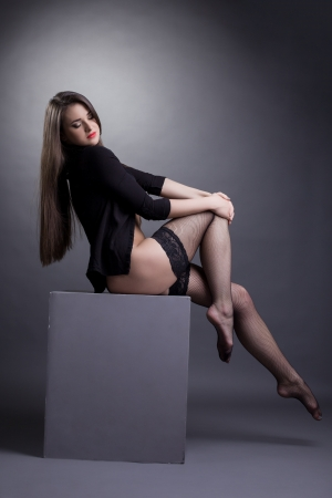 stockings woman: Full length portrait of sexy young brunette sitting on cube in studio in black shirt and lingerie