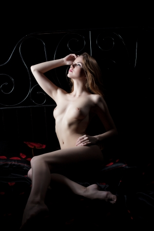Full length portrait of sexy young woman lying naked on bed in dark Stock Photo - 17592868