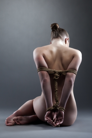 Full length portrait of woman posing with shibari in studio