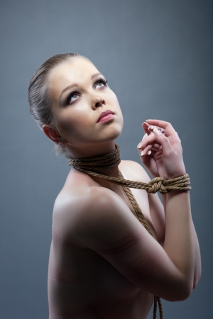 Studio portrait of young woman with shibari Stock Photo - 17597028