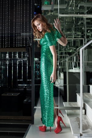 Young woman in green fashion dress walk on stairs in fashion club Stock Photo - 17639447