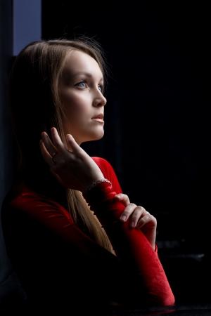 Portrait of beautiful young woman in red dress in dark nightclub photo
