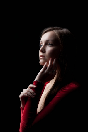 Portrait of beautiful young woman in red dress posing in dark nightclub photo