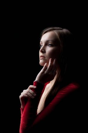 velvet dress: Portrait of beautiful young woman in red dress posing in dark nightclub