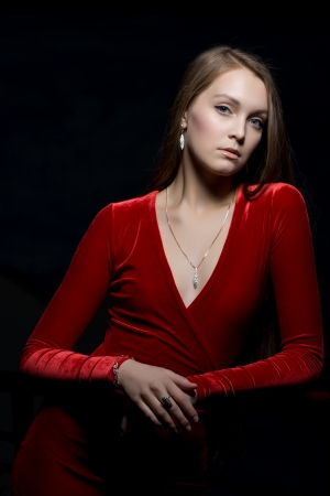 Portrait of beautiful young woman in red dress in dark nightclub photo