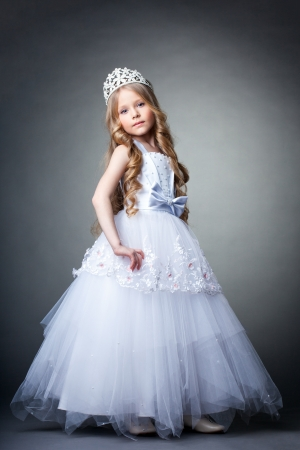 Full length portrait of pretty little girl in tiara and white dress
