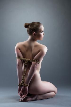 naked body: Studio portarit of nude young woman with shibari sitting on floor