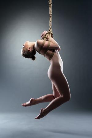 erotico: Piena lunghezza ritratto di giovane donna sottile rilegato con Shibari corda